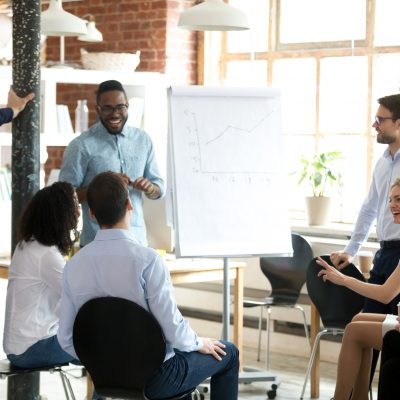 Smiling African American mentor or coach make flipchart presentation for diverse employees, excited black presenter present project on whiteboard, coworkers laugh having fun at casual briefing